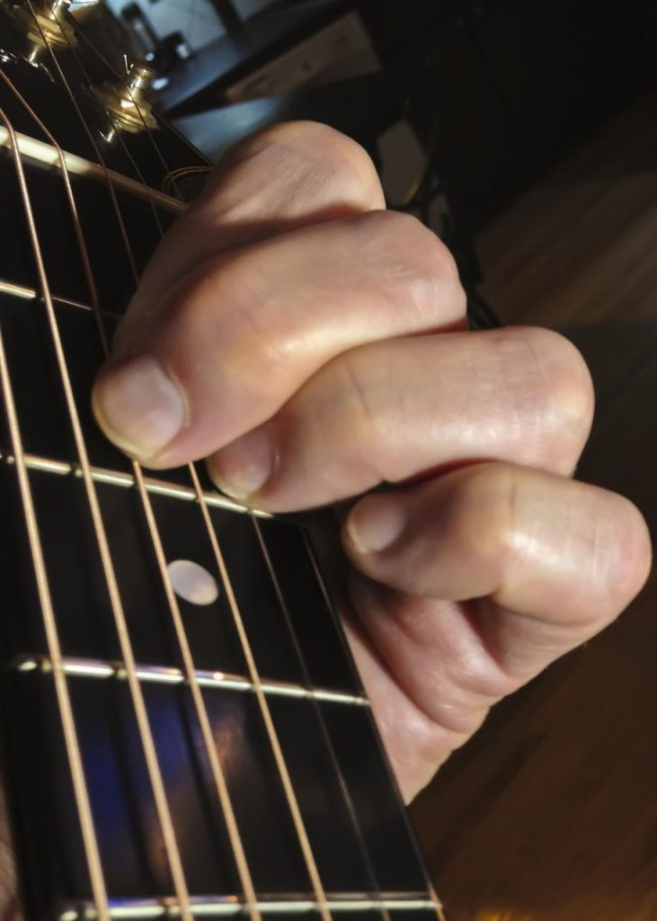 A chord shown with fingers on neck